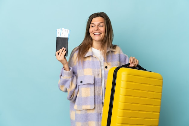 Młoda słowaczka na białym tle na niebieskim tle na wakacjach z walizką i paszportem