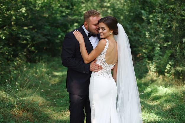 Młoda ślub para cieszy się romantyczne chwile na zewnątrz. namiętne objęcia narzeczonych z zewnątrz narzeczeni na spacerze w słoneczny dzień. ślub dzień ślubu w zielonym parku