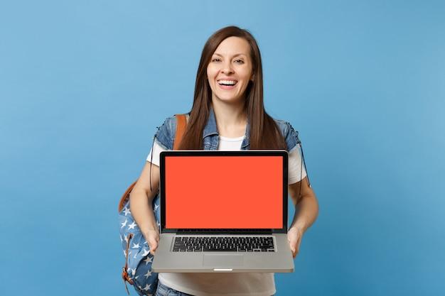 Młoda śmiejąca się kobieta studentka w dżinsowych ubraniach z plecakiem trzymającym komputer typu laptop z pustym czarnym pustym ekranem na białym tle na niebieskim tle. edukacja na studiach. skopiuj miejsce na reklamę.