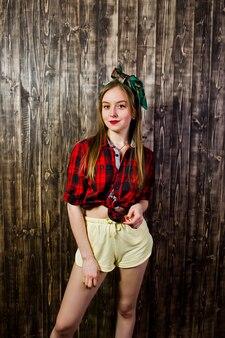 Młoda śmieszna gospodyni domowa w kraciaste koszule i żółte szorty szałowy styl na drewnianej ścianie.