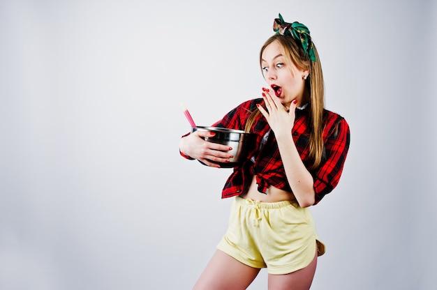 Młoda śmieszna gospodyni domowa w kraciastej koszula i żółtych skrótach upina styl z rondlem i kuchenną łyżką odizolowywającymi