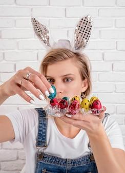 Młoda śmieszna kobieta w uszach królika wkładając kolorowe jajko przepiórcze do plastikowego uchwytu