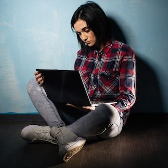 Młoda smutna dziewczyna cierpiąca na uzależnienie od sieci społecznościowych siedzi na podłodze z notebookiem