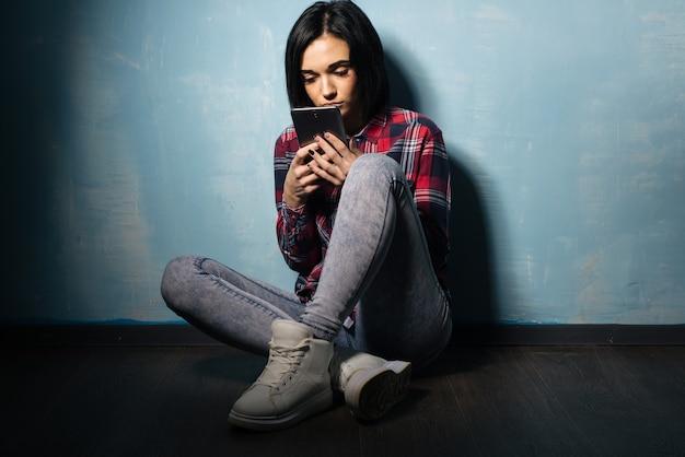 Młoda smutna dziewczyna cierpiąca na uzależnienie od sieci społecznościowych siedzi na podłodze ze smartfonem