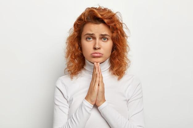 Młoda smutna dziewczyna prosi o coś, trzyma ręce w geście modlitwy, błaga o pomoc, zaciska dolną wargę, wygląda z żałosnym wyrazem twarzy, ma lśniące kręcone włosy, zdrową skórę. tak mi przykro