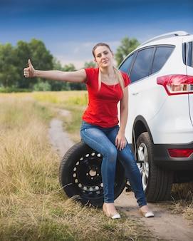 Młoda smutna kobieta siedzi na kole w zepsutym samochodzie i jedzie autostopem