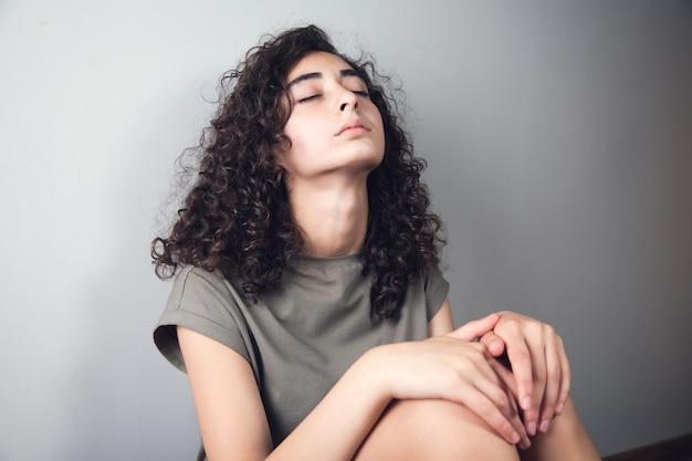 Młoda smutna kobieta siedzi w ziemi.