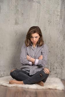 Młoda smutna kobieta w kraciastej koszuli dmucha w policzki.