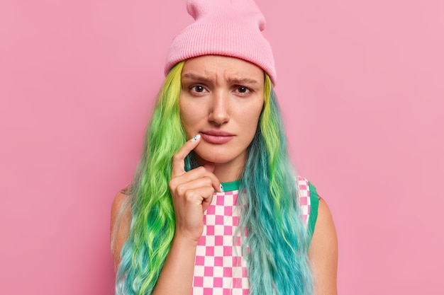 Młoda smutna modelka z długimi farbowanymi włosami trzyma palec w pobliżu kącika ust wygląda na niezadowoloną ma nadąsany wyraz twarzy nosi kapelusz w kratkę na różowym tle