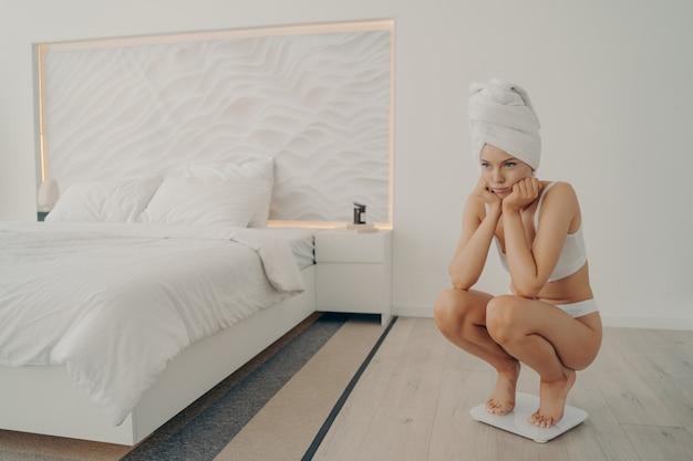 Młoda smutna piękna kobieta w białej bieliźnie stojąca na elektronicznych inteligentnych wagach w sypialni