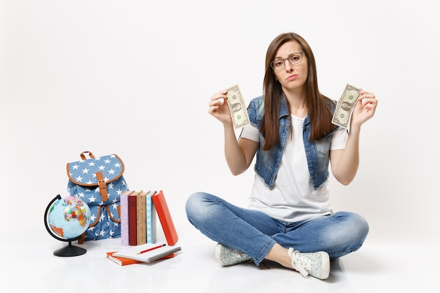 Młoda smutna studentka w okularach trzymająca banknoty dolarowe ma problem z pieniędzmi siedzącymi w pobliżu kuli ziemskiej, plecaka, podręczników szkolnych na białym tle