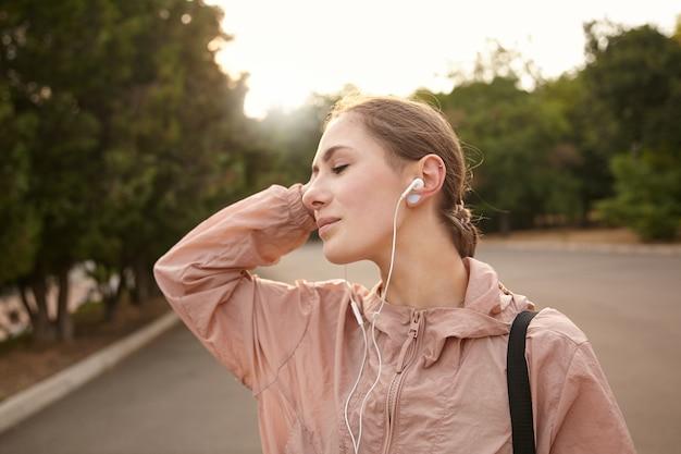 Młoda śniąca pani spacerująca po jodze w parku i słuchająca ulubionej muzyki na słuchawkach, czuje się świetnie i cieszy się dniem.