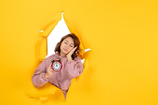 Młoda śpiąca piękna dama trzyma zegar na żółtym rozdartym przełomowym tle