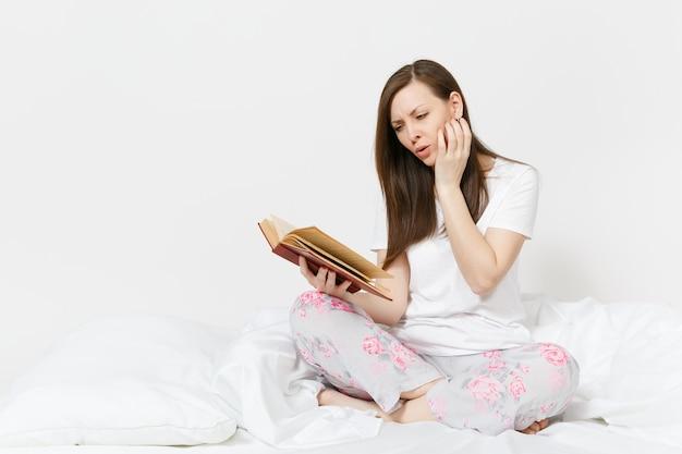 Młoda spokojna kobieta siedzi w łóżku z białym prześcieradłem, poduszką, kocem na białej ścianie