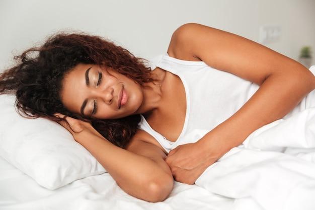 Młoda spokojna kobieta śpi w łóżku w piżamie