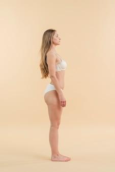 Młoda spokojna kobieta stoi w bieliźnie
