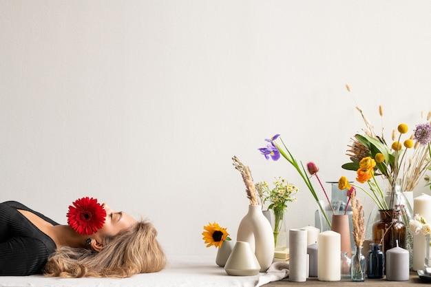 Młoda spokojna kobieta z czerwoną herberą w ustach leżąca wśród różnych świeżych i suszonych kwiatów i polnych kwiatów w wazonach i grupie świec