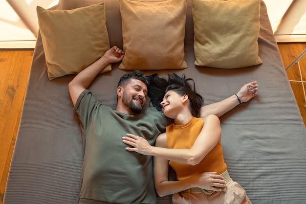 Młoda spokojna para leżąca na łóżku z trzema poduszkami