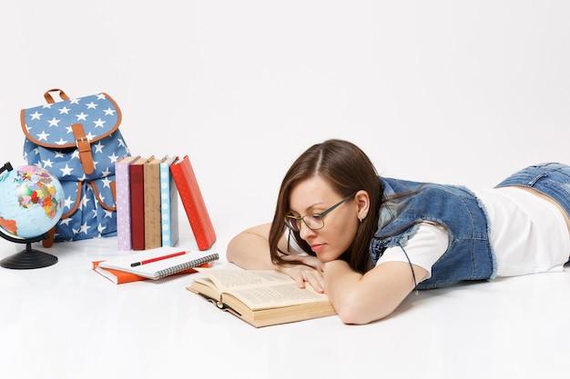 Młoda spokojna piękna studentka w dżinsowych ubraniach i okularach czyta książkę leżącą w pobliżu kuli ziemskiej, plecaka, podręczników szkolnych na białym tle