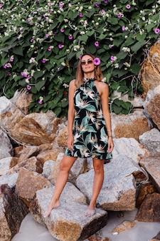 Młoda spokojna wytatuowana kobieta w letniej tropikalnej krótkiej sukience na kamienistej plaży z zielonym krzewem i fioletowymi różowymi kwiatami