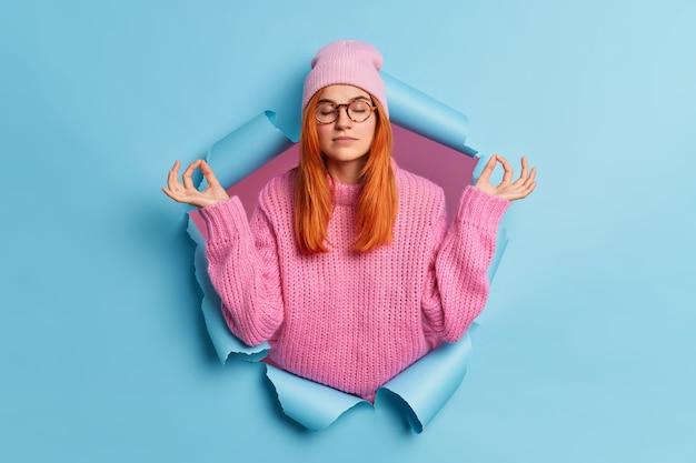 Młoda spokojna, zrelaksowana kobieta trzyma ręce w geście jogi, trzyma oczy zamknięte, medytuje w pomieszczeniu, oddycha głęboko, medytuje w pomieszczeniu.