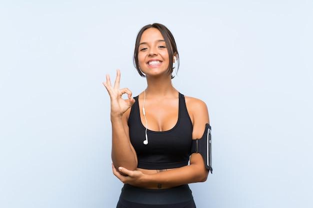 Młoda sport dziewczyna nad odosobnioną błękit ścianą pokazuje ok znaka z palcami