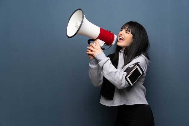 Młoda sport kobieta krzyczy przez megafon