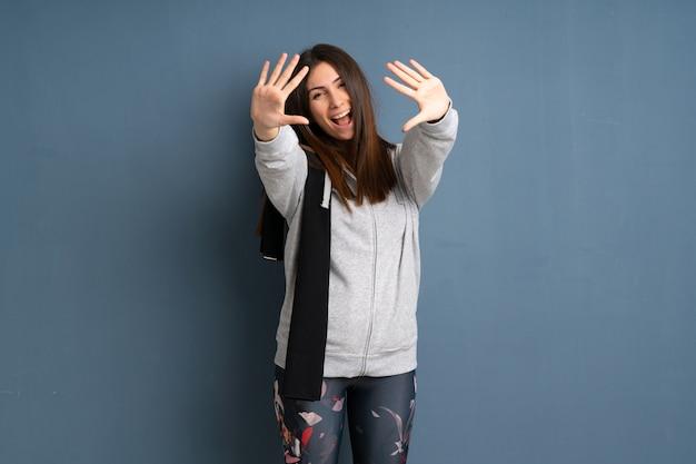 Młoda sport kobieta liczy dziesięć z palcami