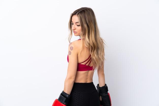 Młoda sport kobieta nad odosobnioną biel ścianą z bokserskimi rękawiczkami