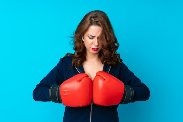 Młoda sport kobieta nad odosobnionym błękitnym tłem z bokserskimi rękawiczkami