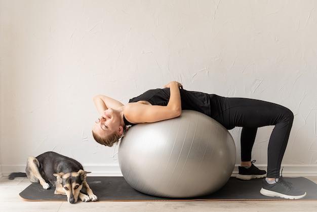 Młoda sportive kobieta leżąc na piłce fitness rozgrzewa się przed treningiem