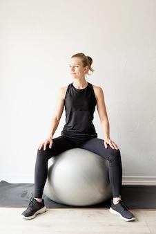 Młoda sportive kobieta siedzi na piłce fitness rozgrzewa się przed treningiem