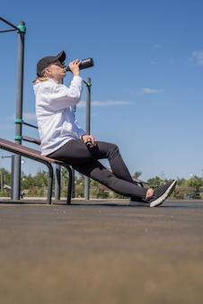 Młoda sportive kobieta w sportowych rękawiczkach woda pitna na boisku sportowym