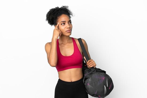 Młoda sportowa afroamerykanka z torbą sportową na białym tle na niebieskim tle ma wątpliwości i myśli