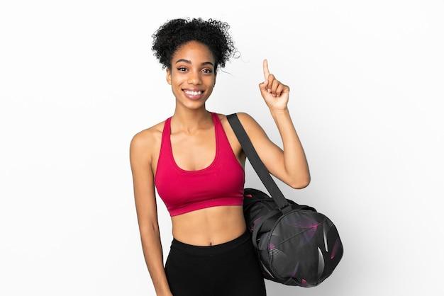 Młoda sportowa afroamerykanka z torbą sportową na białym tle na niebieskim tle pokazująca i unosząca palec na znak najlepszych