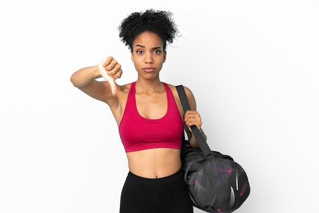 Młoda sportowa afroamerykanka z torbą sportową na białym tle na niebieskim tle pokazującą kciuk w dół z negatywną ekspresją