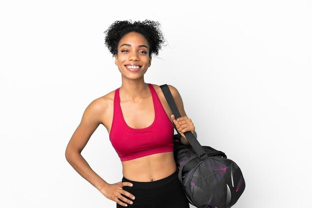 Młoda sportowa afroamerykanka z torbą sportową na białym tle na niebieskim tle pozuje z rękami na biodrach i uśmiecha się