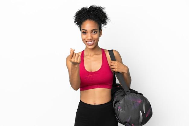 Młoda sportowa afroamerykanka z torbą sportową na białym tle na niebieskim tle robi gest pieniędzy