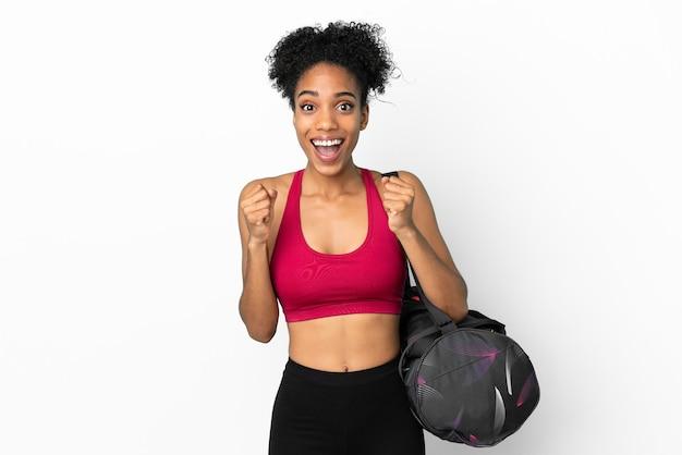 Młoda sportowa afroamerykanka z torbą sportową na białym tle na niebieskim tle świętująca zwycięstwo w pozycji zwycięzcy