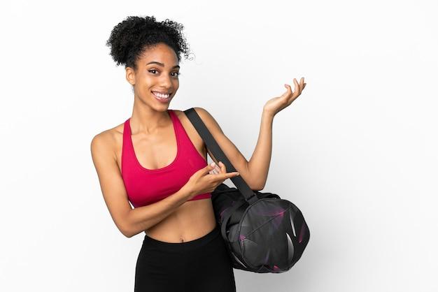 Młoda sportowa afroamerykanka z torbą sportową na białym tle na niebieskim tle wyciągając ręce do boku za zaproszeniem