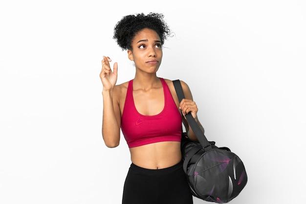 Młoda sportowa afroamerykanka z torbą sportową na białym tle na niebieskim tle z palcami skrzyżowanymi i życzącymi wszystkiego najlepszego