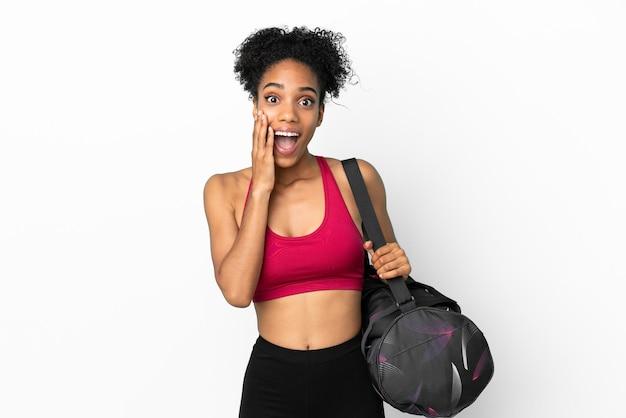 Młoda sportowa afroamerykanka z torbą sportową na białym tle na niebieskim tle z zaskoczeniem i zszokowanym wyrazem twarzy