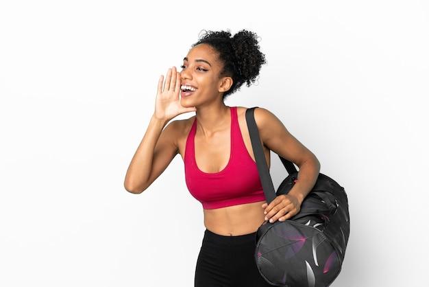 Młoda sportowa afroamerykanka z torbą sportową odizolowaną na niebieskim tle krzyczącą z szeroko otwartymi ustami