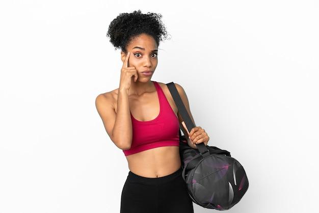 Młoda sportowa afroamerykanka z torbą sportową odizolowaną na niebieskim tle myśląca o pomyśle