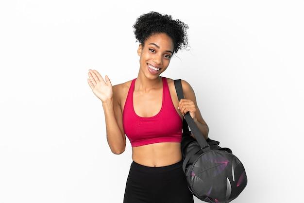 Młoda sportowa afroamerykanka z torbą sportową odizolowaną na niebieskim tle, pozdrawiając ręką ze szczęśliwym wyrazem twarzy
