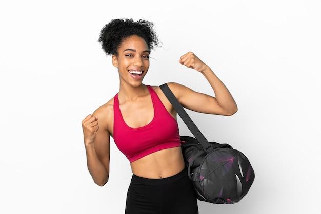 Młoda sportowa afroamerykanka z torbą sportową odizolowaną na niebieskim tle świętuje zwycięstwo