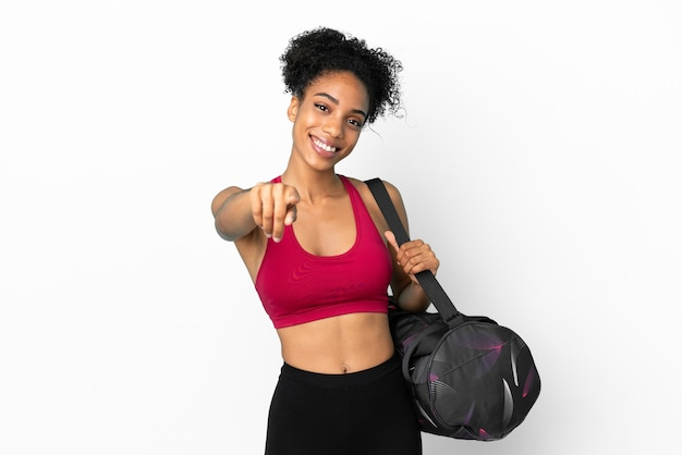 Młoda sportowa afroamerykanka z torbą sportową odizolowaną na niebieskim tle wskazującą przód ze szczęśliwym wyrazem twarzy