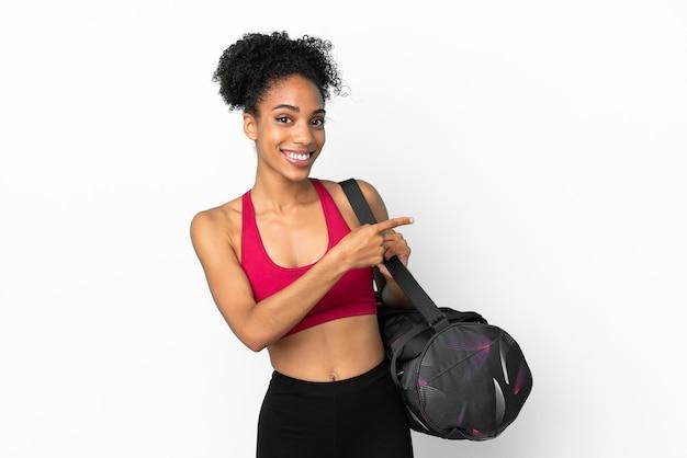 Młoda sportowa afroamerykanka z torbą sportową odizolowaną na niebieskim tle wskazującym palcem w bok