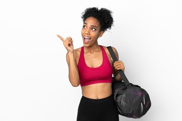 Młoda sportowa afroamerykanka z torbą sportową odizolowaną na niebieskim tle, zamierzająca zrealizować rozwiązanie, podnosząc palec w górę