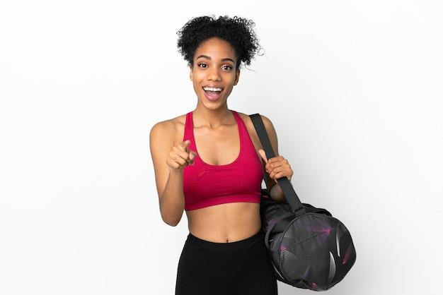 Młoda sportowa afroamerykanka z torbą sportową odizolowaną na niebieskim tle zaskoczona i wskazująca przód